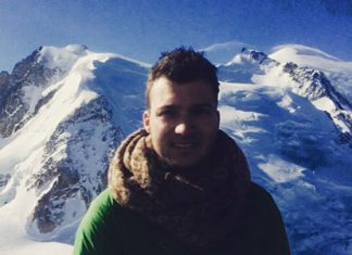 man standing in front of snowy mountains
