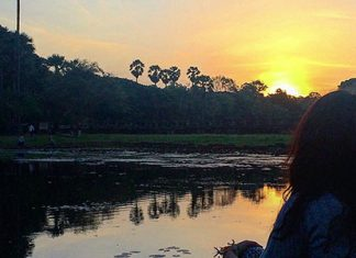 girl watching the sunset by a lake in Cambodia